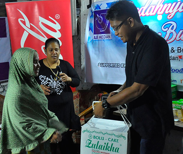 Ketua AJI Medan, Agoez Perdana (kanan) didampingi Sekretaris AJI Medan Fika Rahma (tengah), secara simbolis menyerahkan paket Ramadhan kepada perwakilan kaum dhuafa, pada acara silaturahmi dan buka puasa bersama keluarga besar AJI Medan, Jumat (17/6/2016).